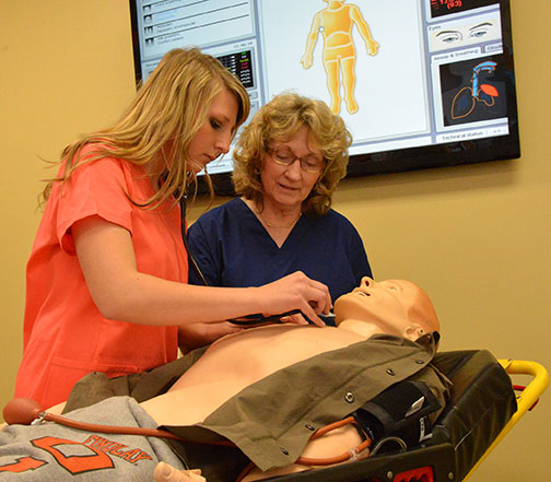 Marjorie Walker (right), observes student working with a nursing lab manikin.