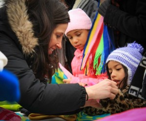 A Susie's Coats volunteer, left, helps children find items during the 2014 giveaway.