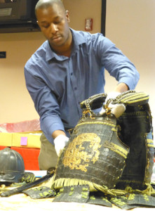University of Findlay student Troylin Banks holds up a piece of samurai armor found in the archives of the Hancock Historical museum. Banks was one of 11 graduate students in a university rhetoric class that worked with the museum to research items in its collection, giving presentations which may also be used for future lectures and exhibits. (Photo by Jeannie Wiley Wolf)