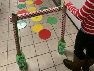 A limbo exercise game made with plastic bottles and cardboard tubing.